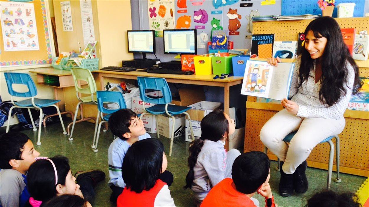 L'enseignante Rahouadja Zarzi montre le livre de contes à ses élèves.