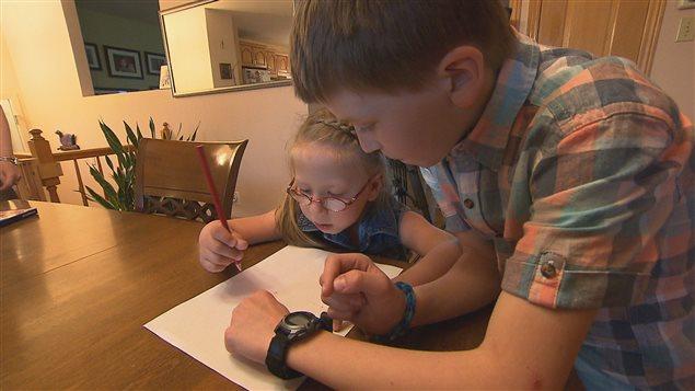 Violette Proulx fait des exercices de dessins avec son frère