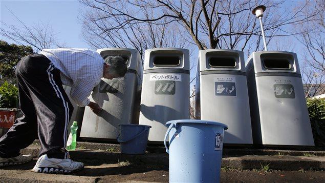 Un homme nettoie des bacs à ordures et à recyclage dans un parc de Tokyo, au Japon.