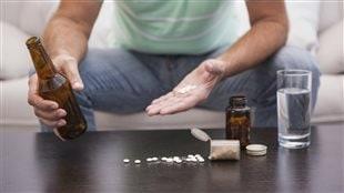 Un homme tient des médicaments dans sa main gauche et tient une bouteille de bière dans sa main droite.