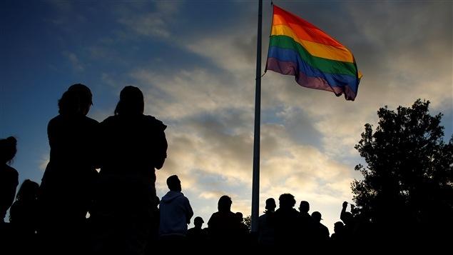 Réunis devant un drapeau arc-en-ciel à la mémoire des victimes de la fusillade d'Orlando, en Floride