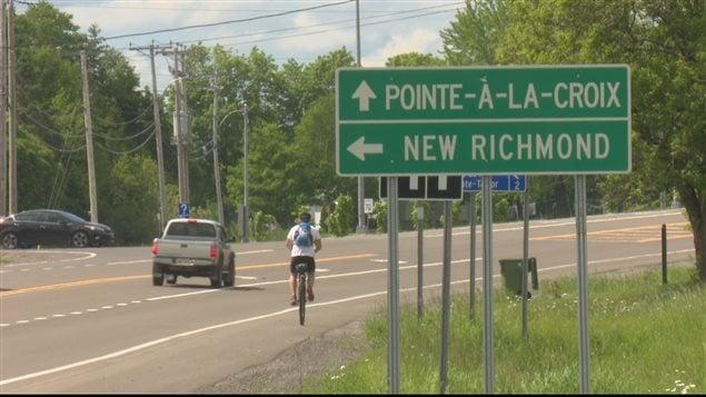 Pierre Olivier Hudon parcourera 700 kilomètres en sept jours. Monocycliste sur le côté du chemin et affiche routière.