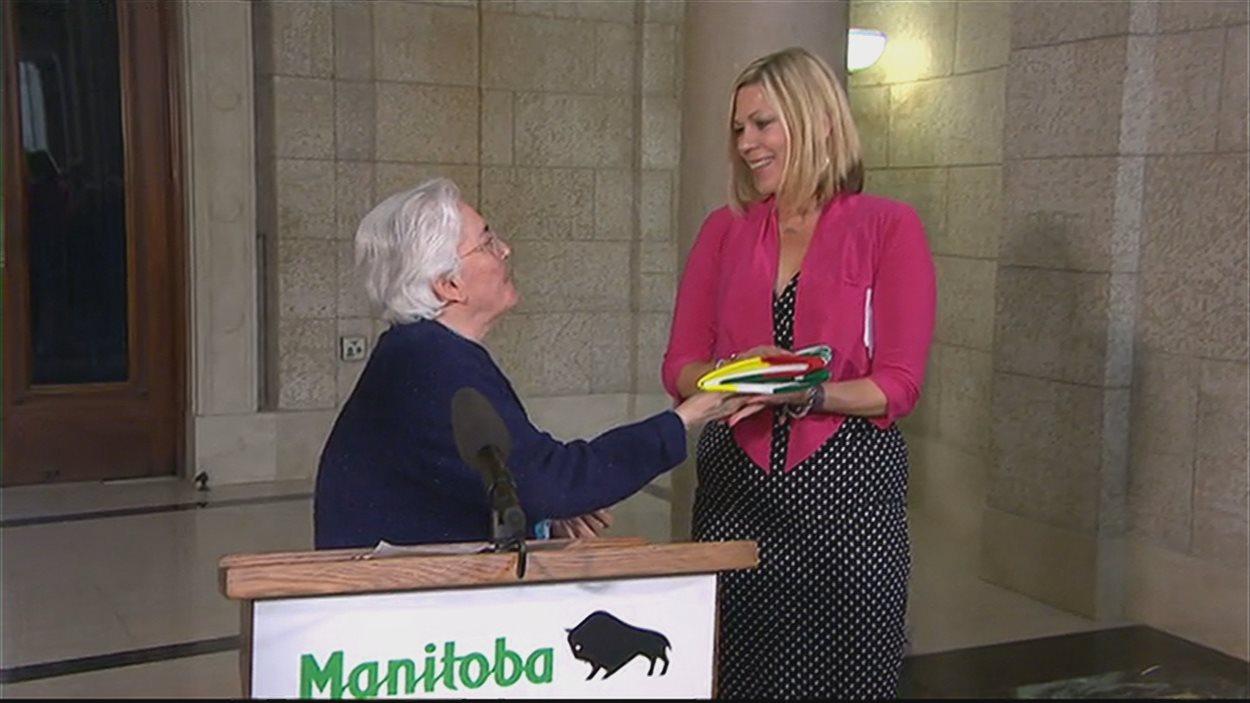 La présidente de la Société franco-Manitobaine Jacqueline Blay (à la gauche) remet un drapeau franco-manitobain à la ministre des Affaires francophones Rochelle Squires