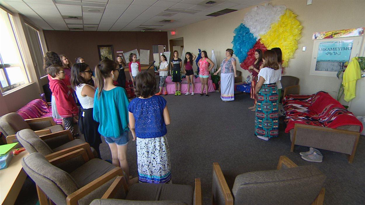 Des jeunes filles en cercle dans une salle.