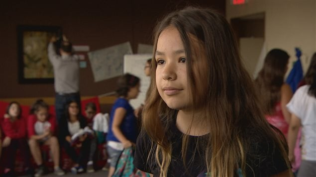 Une jeune fille aux cheveux longs devant un groupe d'adolescentes