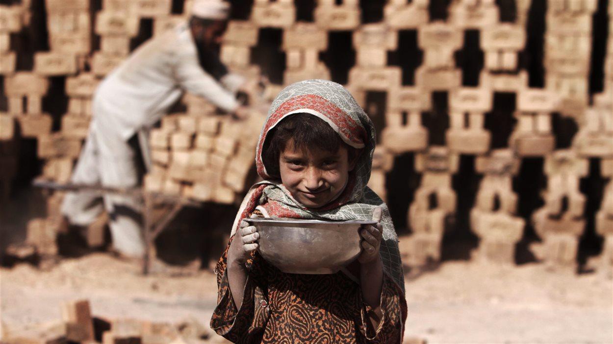 Nagina, 7 ans, pose pour une photo durant ses heures de travail dans une fabrique de briques à Jalalabad, en Afghanistan, le lundi 8 octobre 2012.