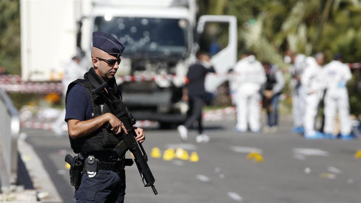 Un policier monte la garde alors que l'enquête se poursuit autour du camion qui a foncé dans la foule rassemblée sur la Promenade des Anglais à Nice lors de la fête nationale.