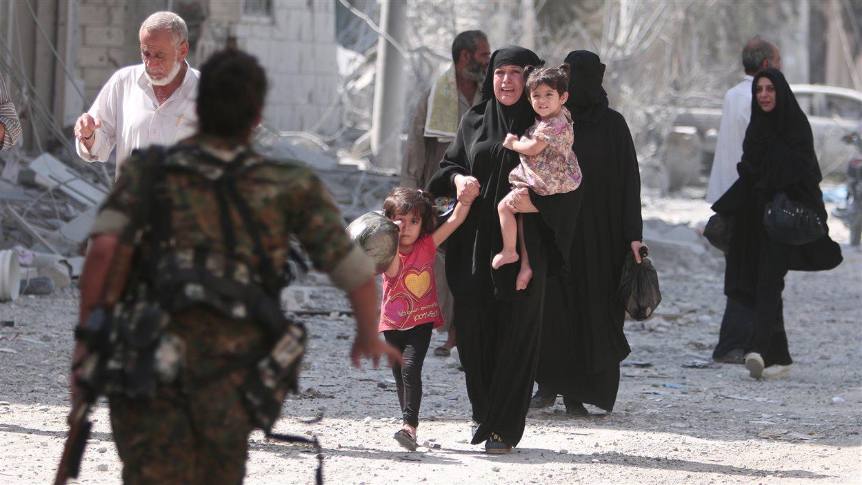 Un soldat rebelle se précipite pour aider des civils évacués d'un quartier de Manbij.