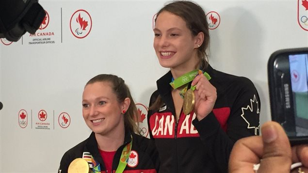 Les porteuses de drapeau Rosie MacLennan et Penny Oleksiak montrent leurs médailles d'or devant le public et les médias à l'aéroport Pearson de Toronto