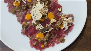 Carpaccio de bison style tataki au jus de viande et champignons, beurre d'argousier et tuiles de Tête à Papineau