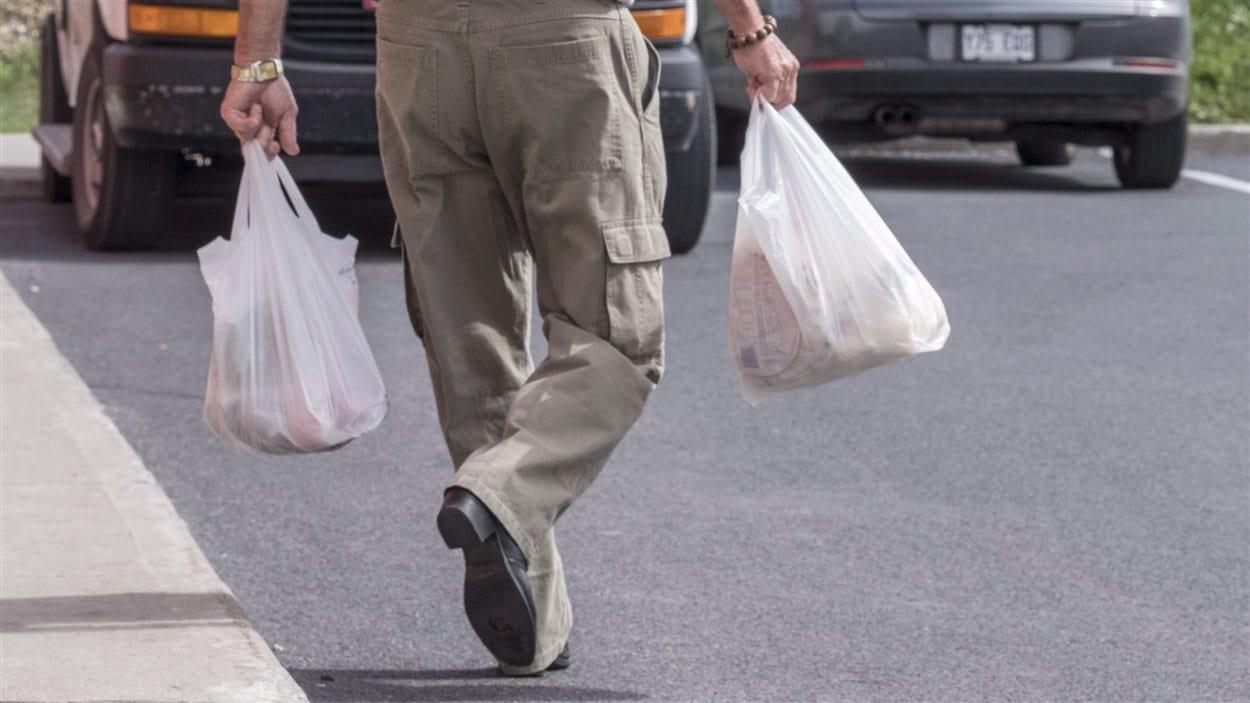 Un consommateur de Brossard transporte ses emplettes dans des sacs en plastique à usage unique, désormais interdits dans cette ville.