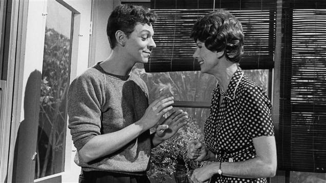 Dans la maison, Clovis Jobin (Marc Labrèche) est debout face à Mme Dessaules (Béatrice Picard) qui lui sourit.