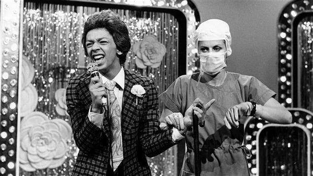 Sur une scène, un chanteur crooner (Normand Brathwaite) est examiné par un docteur (Michèle Deslauriers).