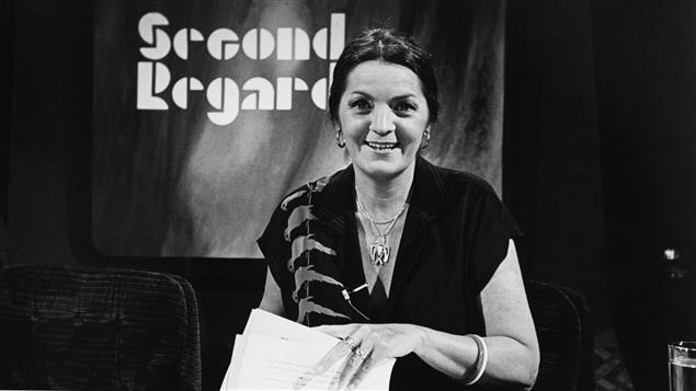 Dans un studio de télévision, l'animatrice Myra Cree, souriante, est assise à un bureau avec des documents dans les mains. Un écran en arrière-plan affiche le nom de l'émission.