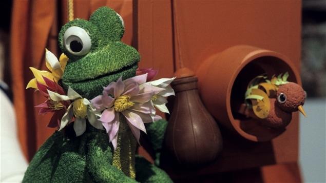 Dans une boutique d'antiquités, la grenouille Virginie (voix de Francine Ruel) est assise à côté d'un tuyau par lequel un petit oiseau sort la tête.