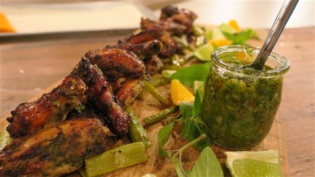 Gros plan d'une planche en bois avec des ailes de poulet et un pot de sauce verte.