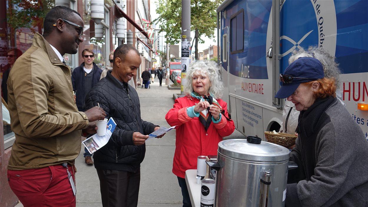 Des bénévoles de la Société Saint-Vincent-de-Paul distribuent café et biscuits aux passants