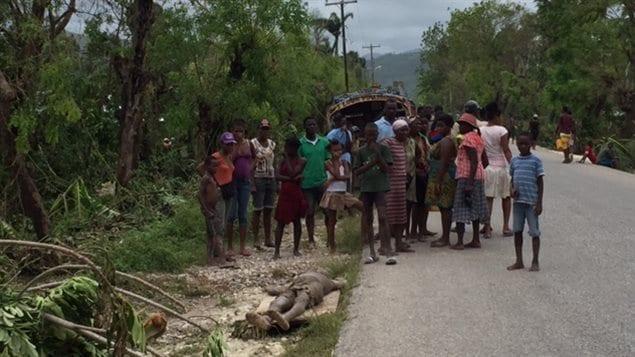 Des gens se recueillent autour d'une victime de l'ouragan Matthew.