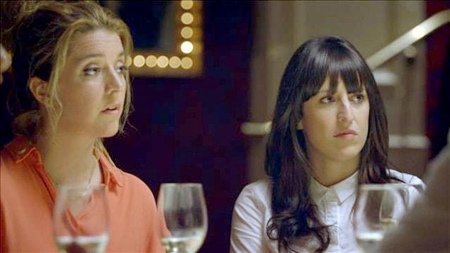 Les comédiennes Marie-Ève Perron et Anne-Élisabeth Bossé son attablées devant une coupe de vin et écoutent la conversation.