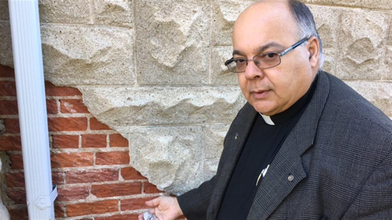 Le père Eugéne Roy montre les murs abîmés de l'église