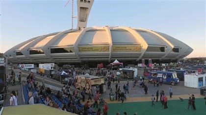 Avec le Stade olympique en arrière-plan, une vue d'ensemble de plusieurs camions de bouffe de rue stationnés sur l'esplanade.