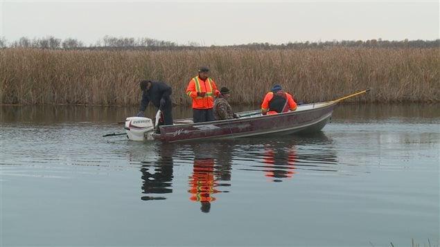 Suivant de nouvelles informations au sujet de sa fille, Wilfred Catcheway et un groupe de bénévoles cherchent dans une rivière près de Duck Bay au Manitoba.