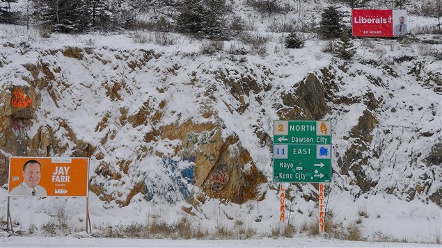 La campagne électorale au Yukon, des affiches des candidats sur un terrain escarpé et enneigé