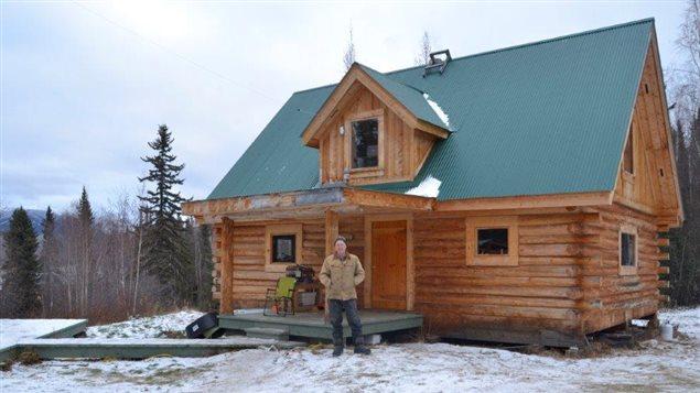 Norm Carlson devant sa maison en rondins