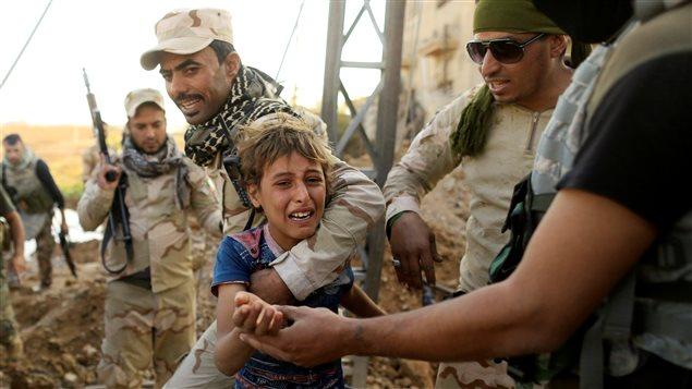 Un enfant irakien pleure dans les bras d'un soldat irakien dans le quartier d'Intisar, à Mossoul.