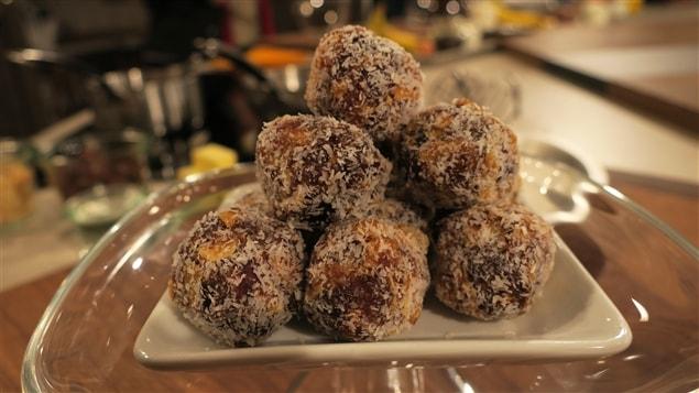 Des boulettes aux dattes et aux noix enrobées de noix de coco, empilées en pyramide dans une assiette blanche.