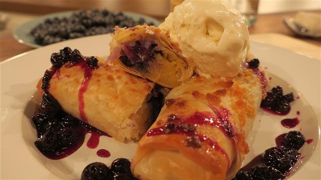 Des petits rouleaux de pâte phyllo frite, avec une purée de bleuets et une boule de glace à la vanille