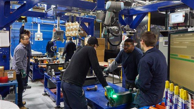 Des employés qui entourent des robots d'inspection chez Spectra Premium à Boucherville.