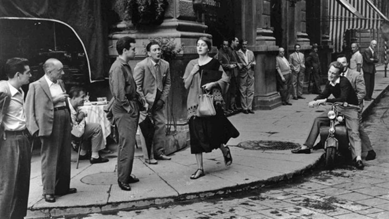 Un photo en noir et blanc d'une dame qui marche dans une rue où plusieurs hommes la reluquent.