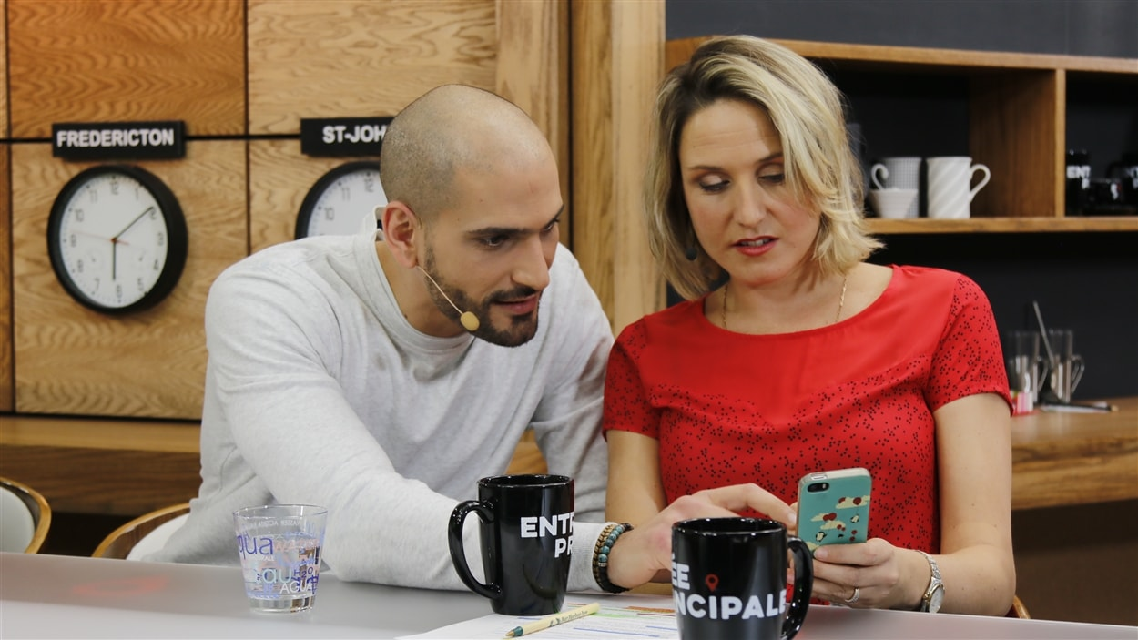 Pascale montre quelque chose sur son téléphone intelligent à Raed.