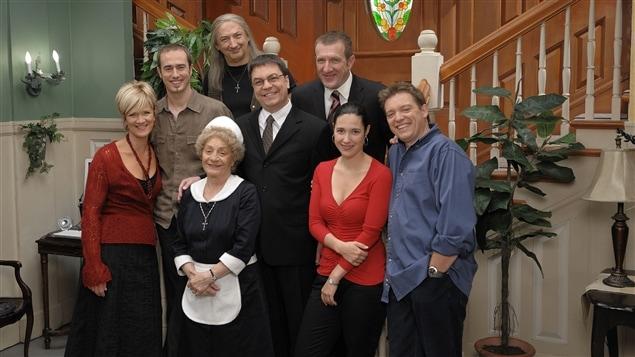 Les personnages de L'auberge du chien noir sont réunis au bas de l'escalier.